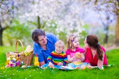 Beautiful young family with kids having picnic outdoors. Young family with kids having picnic outdoors. Parents with two children relax in a blooming summer Stock Image