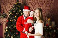 Beautiful young family with little cute baby girl on Christmas Stock Images