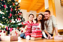 Young family with daughter at Christmas tree at home. Royalty Free Stock Images