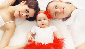 Beautiful young family lying together on the bed at home Royalty Free Stock Photography