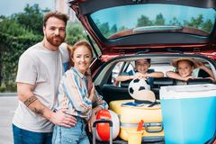 Beautiful young family packing luggage. In car trunk royalty free stock image