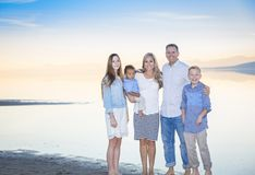 Beautiful Young family portrait on the beach. An elegant and beautiful young family portrait at the beach. Smiling and happy diverse group with a mixed race stock images