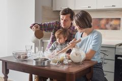 beautiful young family preparing dough stock photo