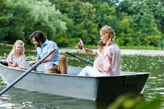 beautiful young family riding boat on lake using tablet and playing royalty free stock photos