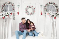 Beautiful young family sitting on porch of christmas decor house royalty free stock photography