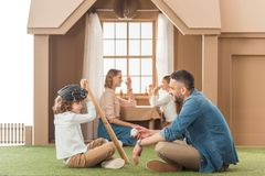 Beautiful young family spending time together. At cardboard house Stock Photo