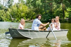 beautiful young family spending time together in boat on river stock photo