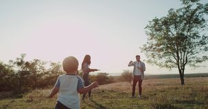 Beautiful young family two childrens three years old and one years old , mom and dar at nature playing together at stock video footage