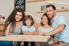 Beautiful young family with two kids waiting for order. In restaurant stock image
