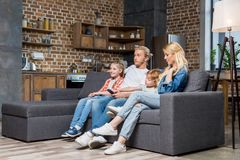 beautiful young family with two kids watching tv royalty free stock photo