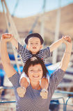 Beautiful young family of two walking along wooden jetty. Woman with son on pier Stock Photography