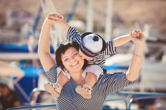 Beautiful young family of two walking along wooden jetty. Woman with son on pier Stock Images