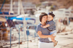 Beautiful young family of two walking along wooden jetty. Woman with son on pier Stock Photos