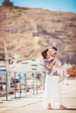 Beautiful young family of two walking along wooden jetty. Woman with son on pier Stock Photo