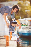 Beautiful young family of two walking along wooden jetty. Woman with son on pier Stock Image