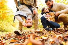 Beautiful young family on a walk in autumn forest. Beautiful young family on a walk in forest having fun. Mother and father with their two sons in warm clothes Royalty Free Stock Images