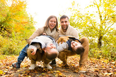 Beautiful young family on a walk in autumn forest. Royalty Free Stock Images
