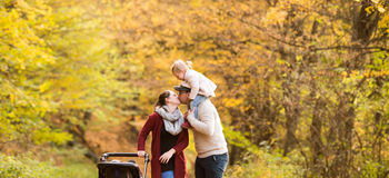 Beautiful young family on a walk in autumn forest. Beautiful young family on a walk in forest. Father giving his daughter piggyback and kissing mother with her Royalty Free Stock Photo