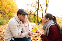 Beautiful young family on a walk in autumn forest. Royalty Free Stock Photography
