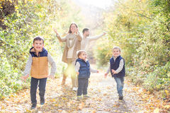 Beautiful young family on a walk in autumn forest. Beautiful young family on a walk in forest. Mother and father with their three sons in warm clothes outside Royalty Free Stock Photo