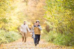 Beautiful young family on a walk in autumn forest. Stock Photos