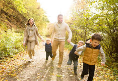 Beautiful young family on a walk in autumn forest. Royalty Free Stock Photos