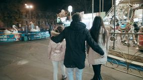 A beautiful young family is walking in the evening in the amusement park. Family vacation in the lunapark. The young family came to the amusement park to rest stock video