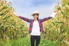 A beautiful young farmer stands holding a corn and smiles happily. stock photo