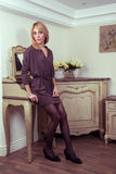 Beautiful young fashion blonde model posing near secretaire. Stock Photos