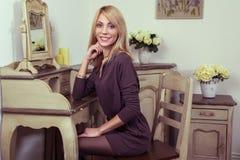 Beautiful young fashion blonde model posing near secretaire. Stock Image