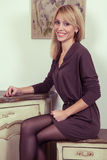 Beautiful young fashion blonde model posing near secretaire. Royalty Free Stock Photography