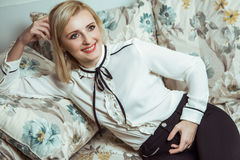 Beautiful young fashion caucasian blonde model posing on sofa. Stock Photography
