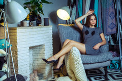 Beautiful young fashion caucasian model posing near armchair. royalty free stock images
