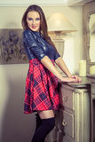 Beautiful young fashion caucasian model posing next to commode. Beautiful young fashion caucasian model in blue and red and scottish cell dress and black shoes royalty free stock photography