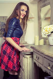Beautiful young fashion caucasian model posing next to commode. Beautiful young fashion caucasian model in blue and red and scottish cell dress and black shoes royalty free stock photo