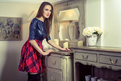 Beautiful young fashion caucasian model posing next to commode. Beautiful young fashion caucasian model in blue and red and scottish cell dress and black shoes stock images