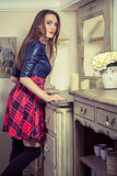 Beautiful young fashion caucasian model posing next to commode. Beautiful young fashion caucasian model in blue and red and scottish cell dress and black shoes royalty free stock image