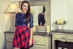 Beautiful young fashion caucasian model posing next to commode. Beautiful young fashion caucasian model in blue and red and scottish cell dress and black shoes stock photos