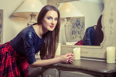 Beautiful young fashion caucasian model posing next to commode. Beautiful young fashion caucasian model in blue and red and scottish cell dress and black shoes royalty free stock photos