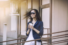 Beautiful young fashion gir with take-away coffee in hand Royalty Free Stock Images