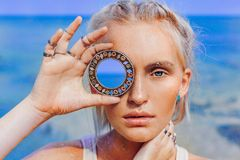 Beautiful young fashion model on the beach. Close up portrait of boho model holding small mirror at her eye stock photo