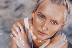 Beautiful young fashion model on the beach. Close up portrait of boho model with sparkling boho accessories stock image