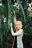 Stunning caucasian female fashion model posing in jungle. Beautiful young fashion model with curly blonde hair wearing black dress and white lace cardigan posing stock photography