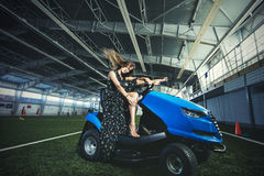 Beautiful young fashion model in a dress at a large sports stadium for the car care coating. Posing stock photo