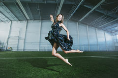 Beautiful young fashion model in a dress at a large sports stadium stock photography