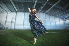 Beautiful young fashion model in a dress at a large sports stadium royalty free stock photo