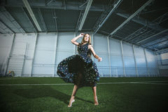 Beautiful young fashion model in a dress at a large sports stadium royalty free stock images