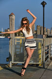 Beautiful young fashion model posing pretty on the pier Stock Images