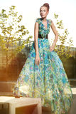 Beautiful young fashion woman in color dress posing outdoor royalty free stock photo