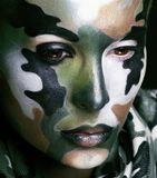 Beautiful young fashion woman with military style clothing and face paint make-up, khaki colored royalty free stock images
